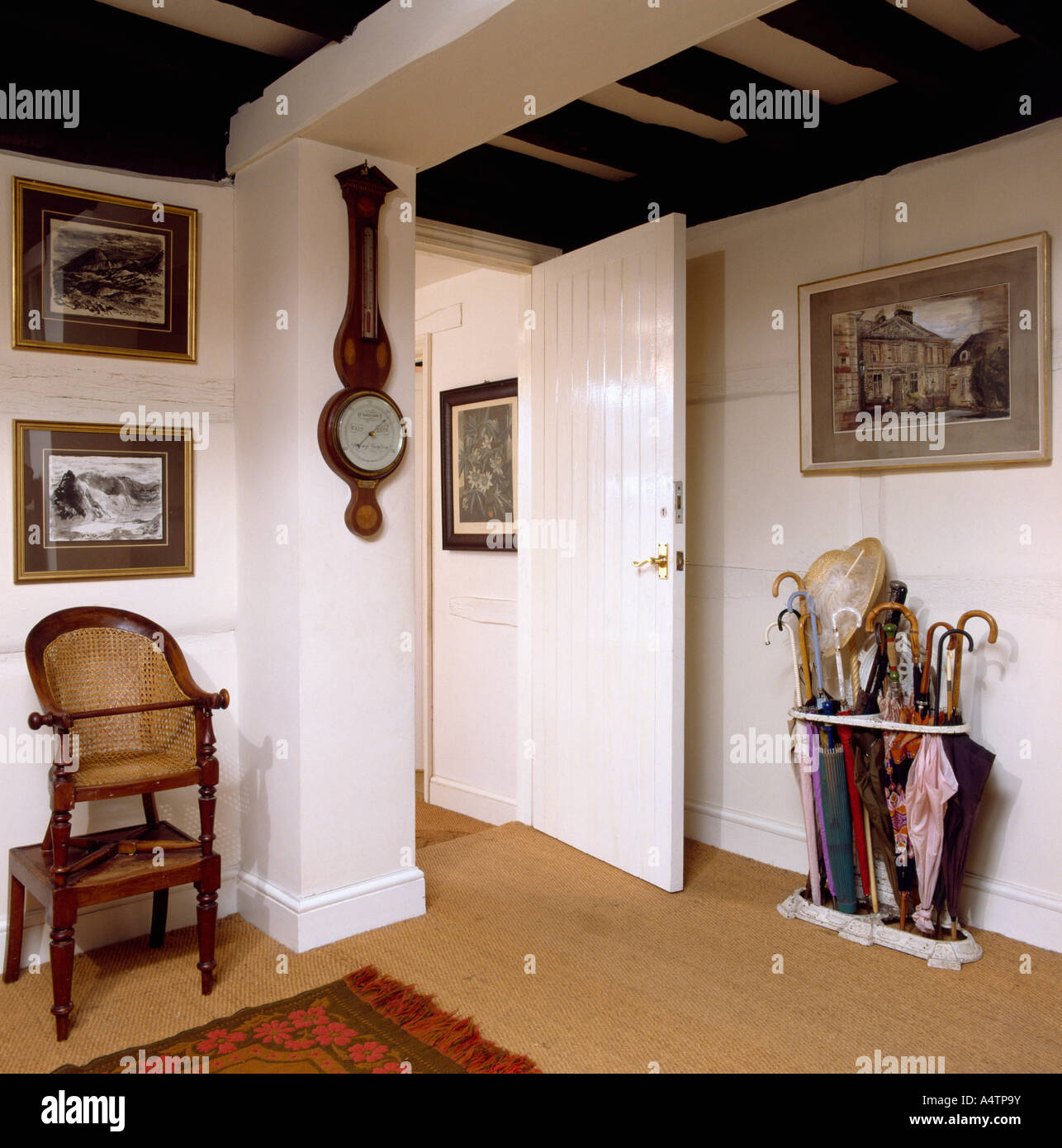 White cottage hall with barometer on wall and antique baby chair on sisal carpet - Stock Image