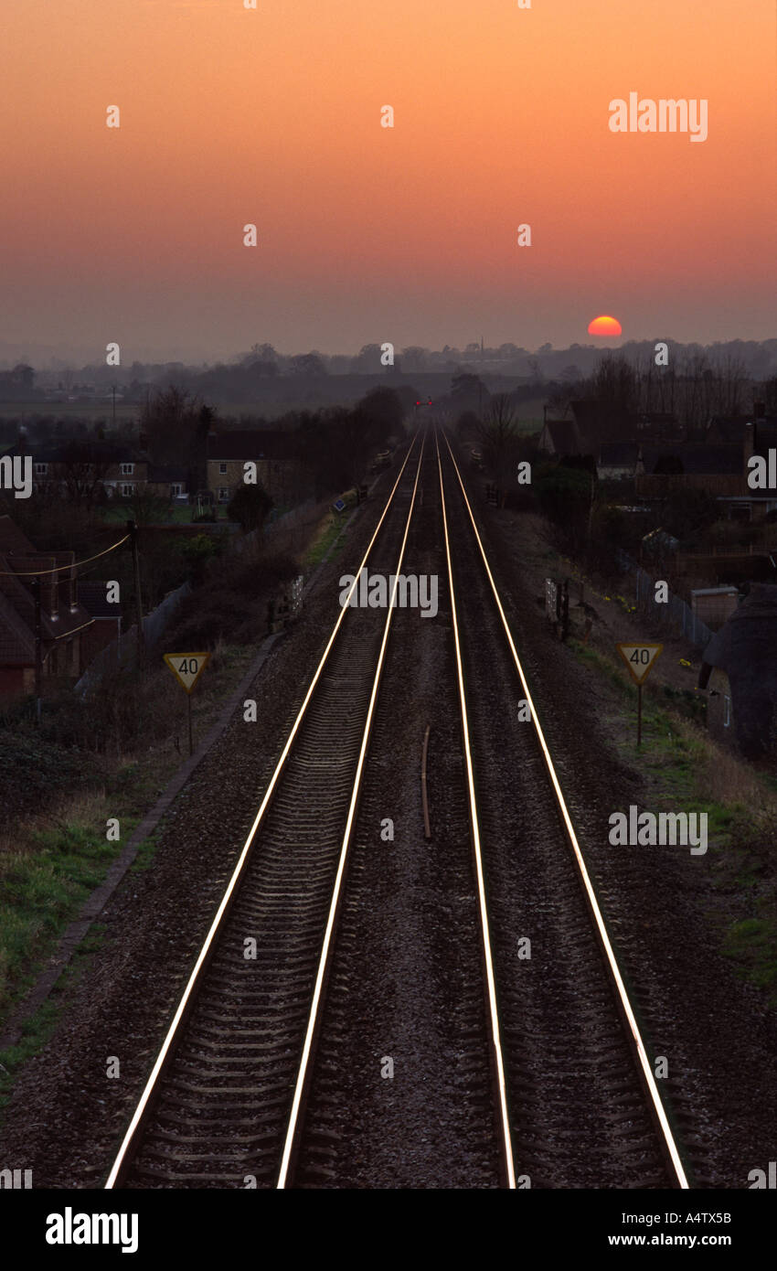 Railway leading to the sun setting on the horizon in Bradford Abbas village Dorset county England UK - Stock Image