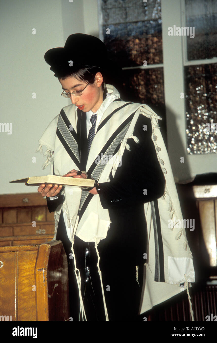 Young Jewish man wearing a tallit reads from a torah in the synagogue JU1225PG - Stock Image