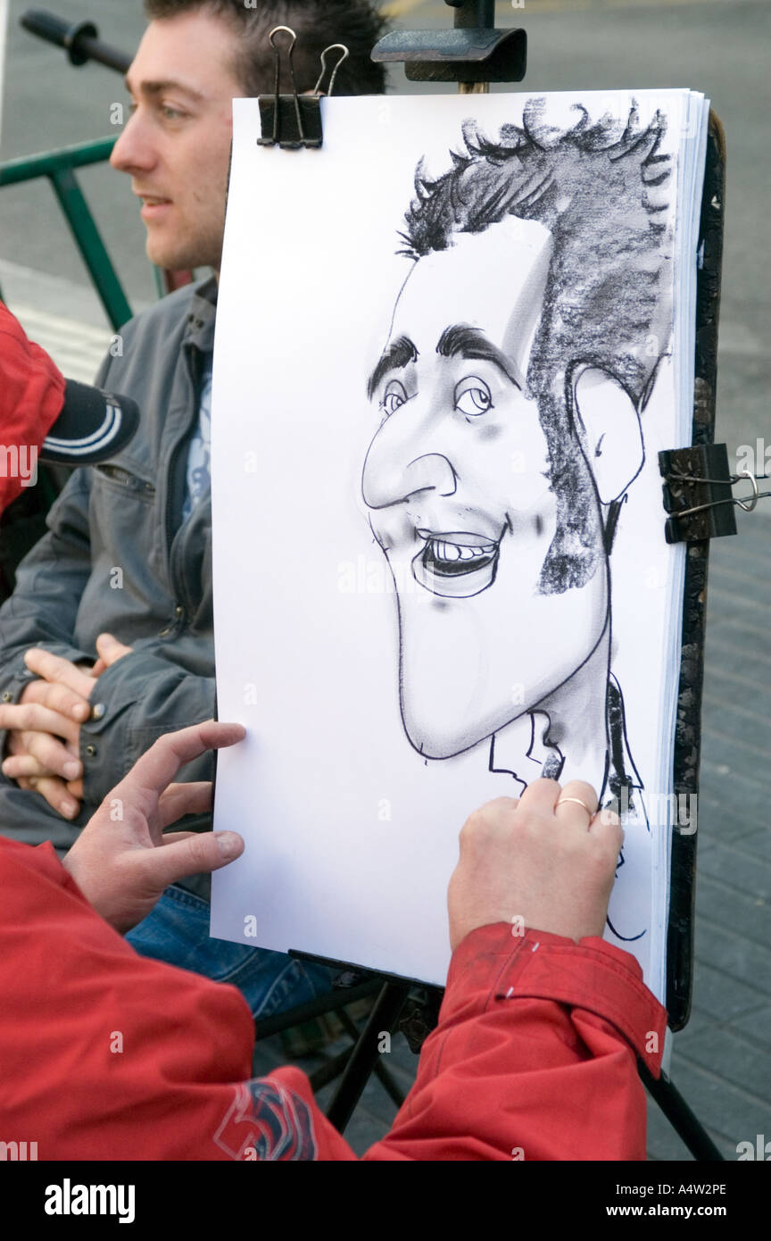 Young man has a caricature drawing made on La Rambla Barcelona Spain - Stock Image