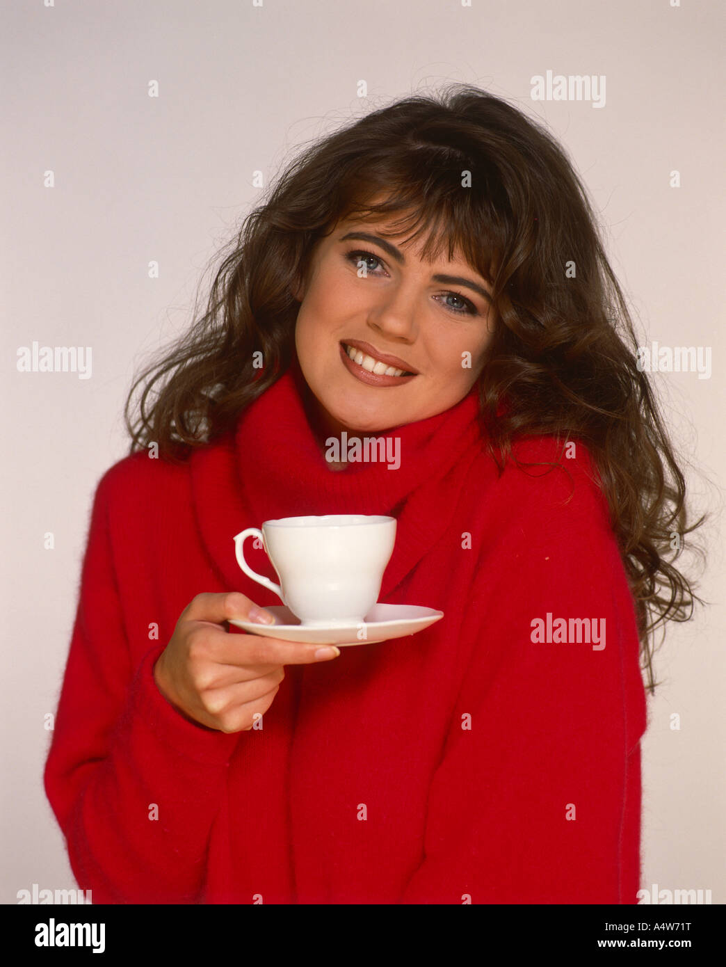 ANGELA LEA IN RED SWEATER WHITE CUP AND SAUCER - Stock Image