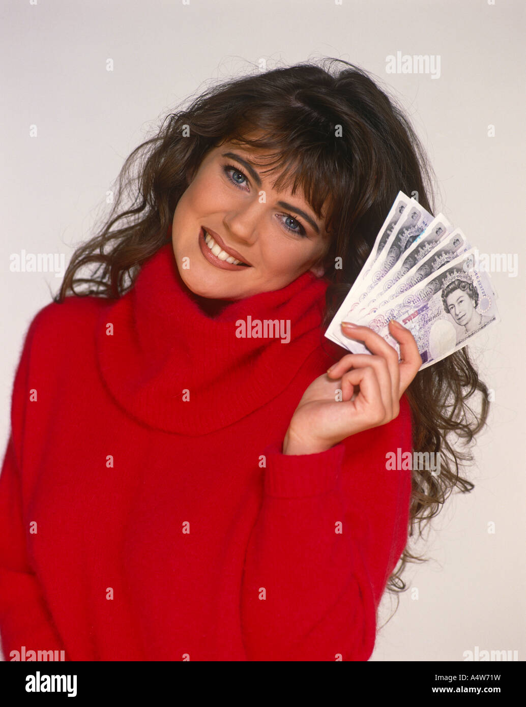 ANGELA LEA IN RED SWEATER HOLDING HANDFUL OF NOTES - Stock Image