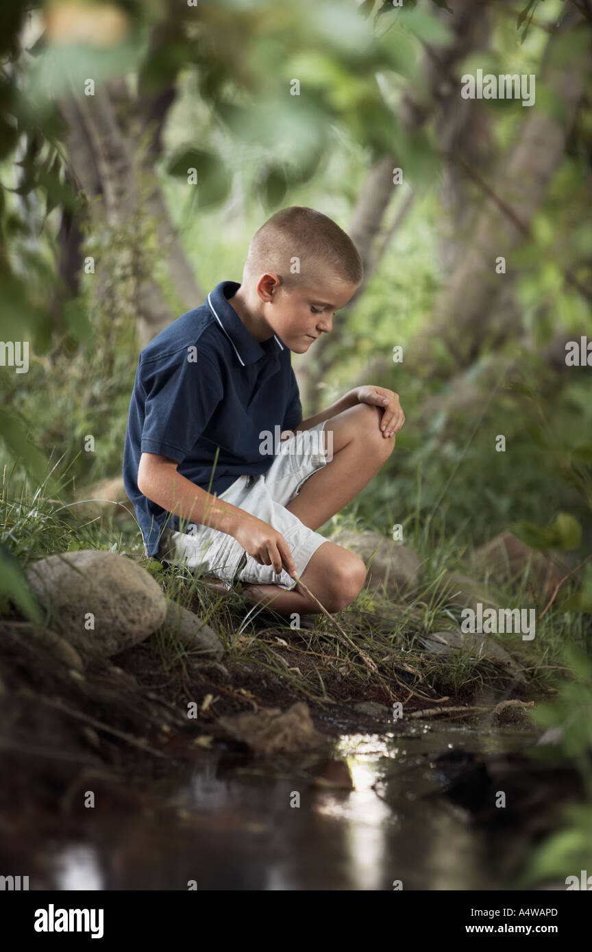 Young boy exploring stream with stick - Stock Image