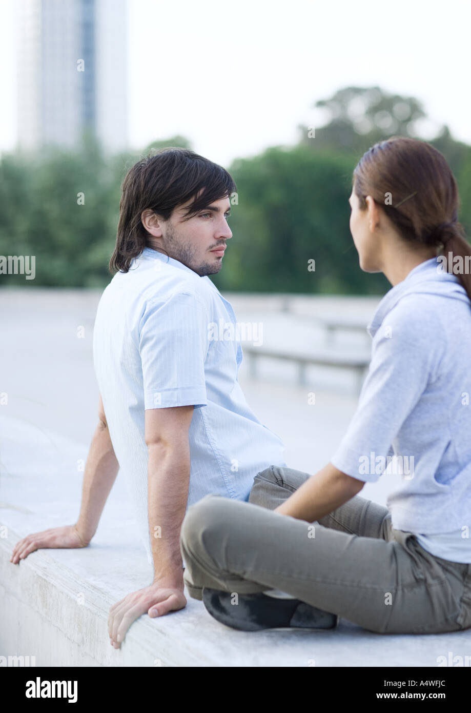 Young couple sitting in urban park - Stock Image