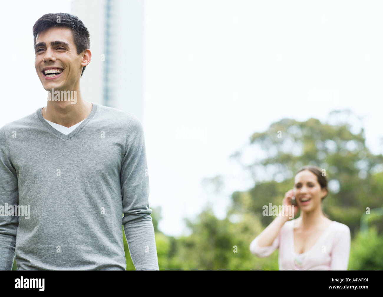 Young man and woman in urban park - Stock Image