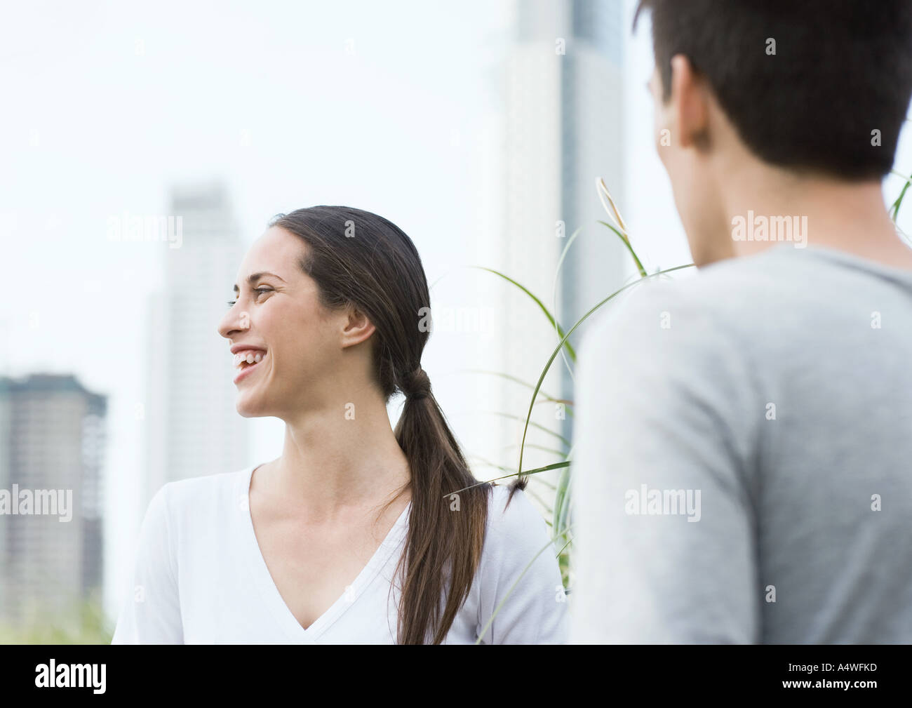 Young woman laughing, with young man - Stock Image