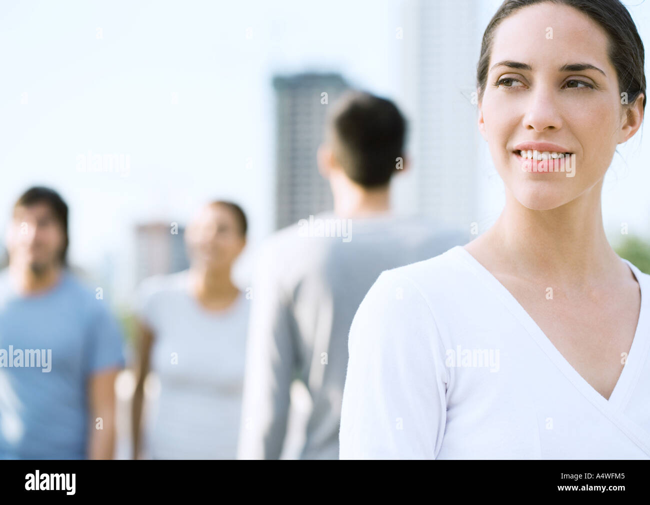 Young woman looking into distance, in urban setting - Stock Image