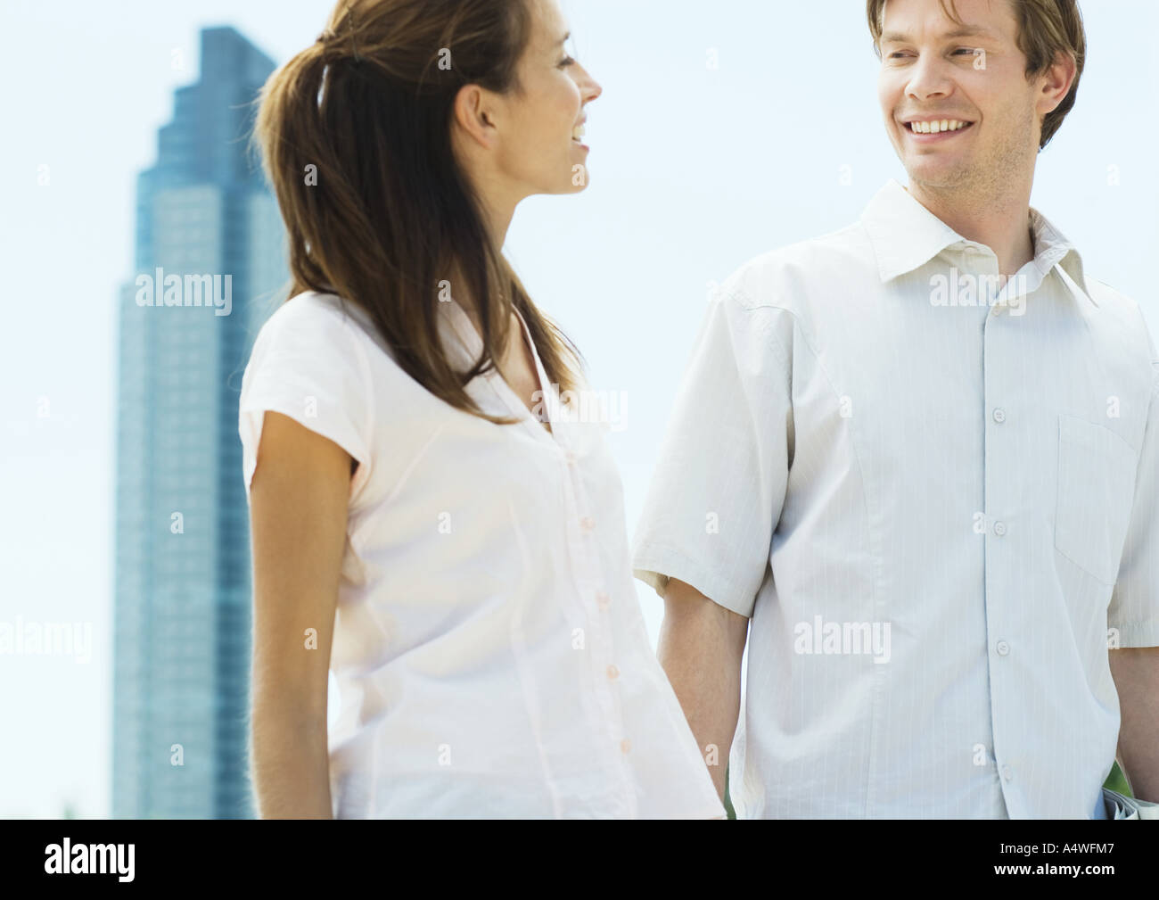 Young couple smiling at each other in urban setting - Stock Image