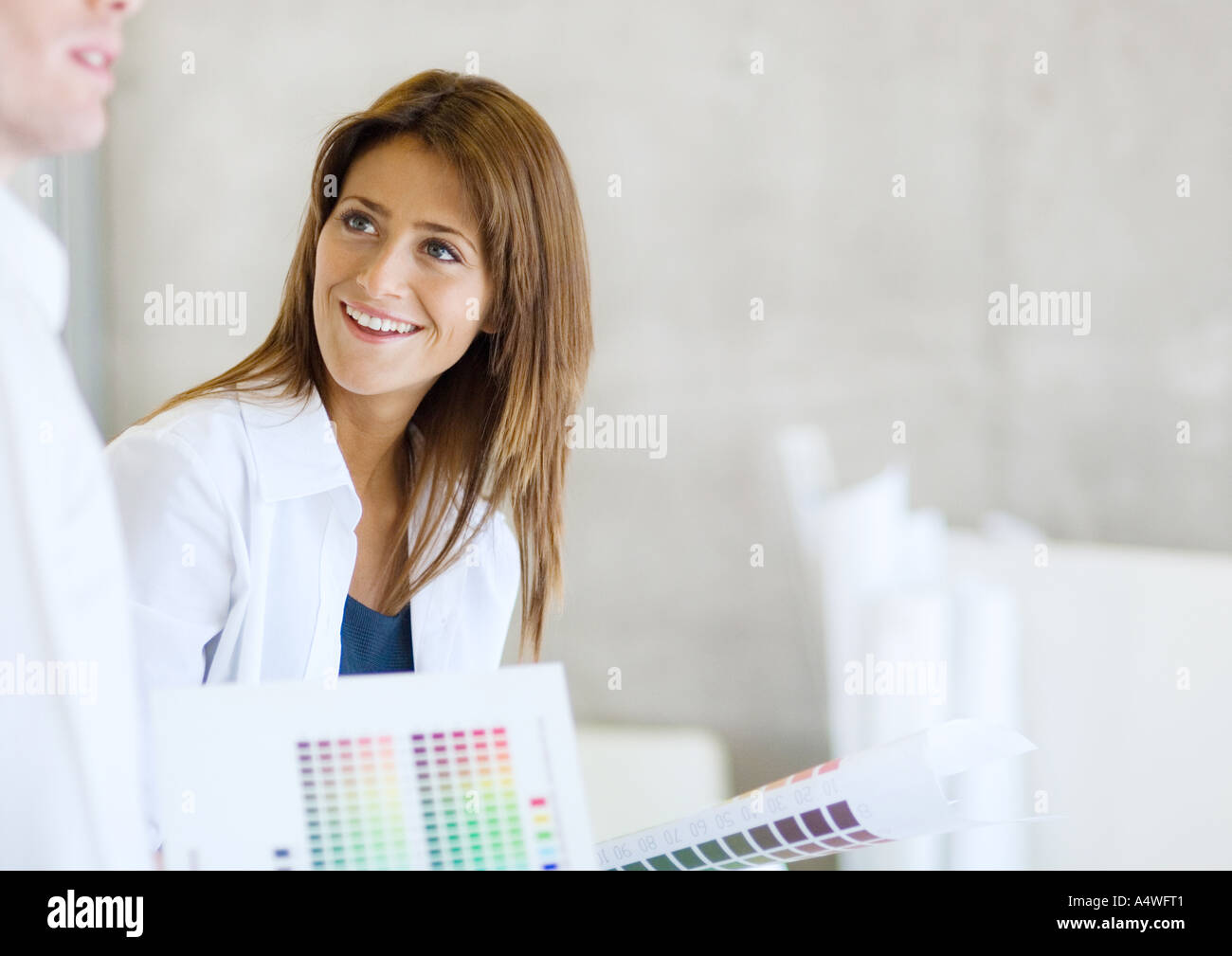 Interior decorator with color swatches smiling at colleague - Stock Image