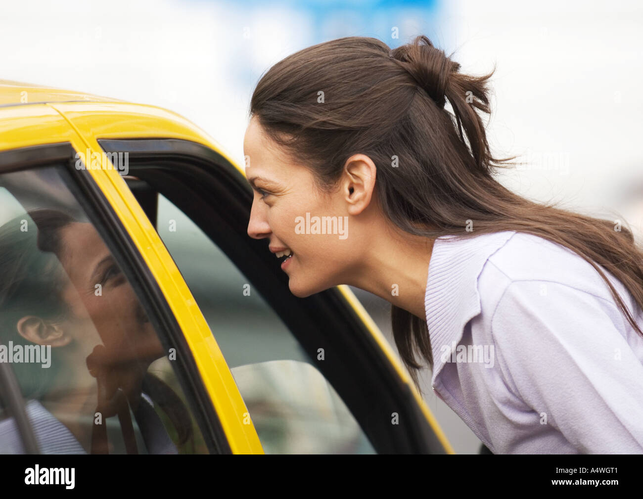 Young woman leaning toward taxi, speaking - Stock Image