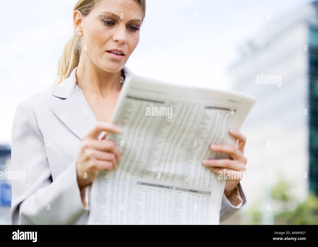 Businesswoman reading financial pages of newspaper - Stock Image