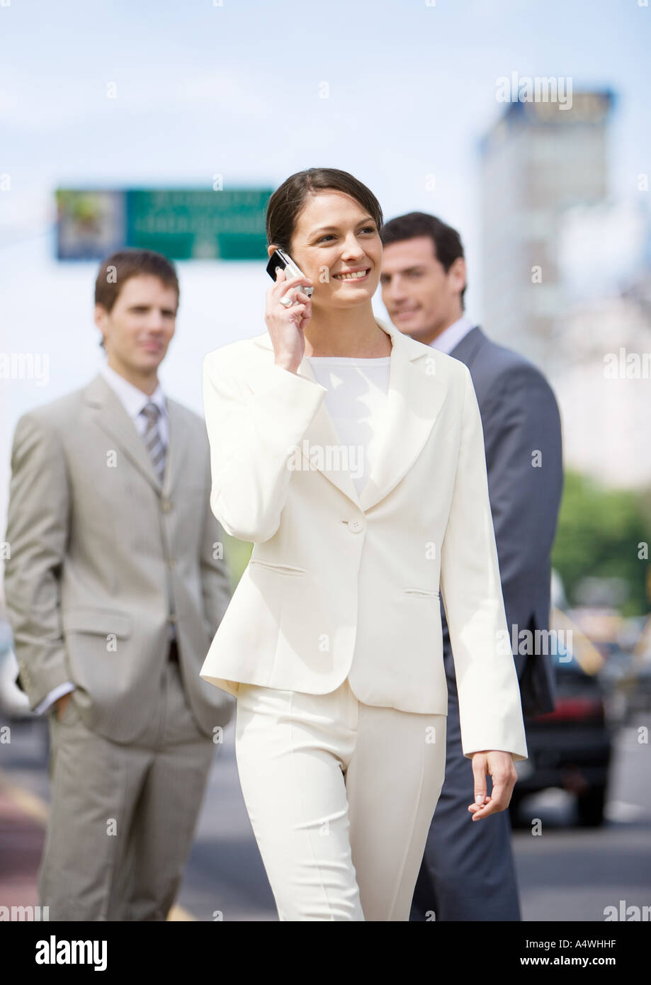 Young businesswoman walking and using cellphone while two businessmen watch in background Stock Photo