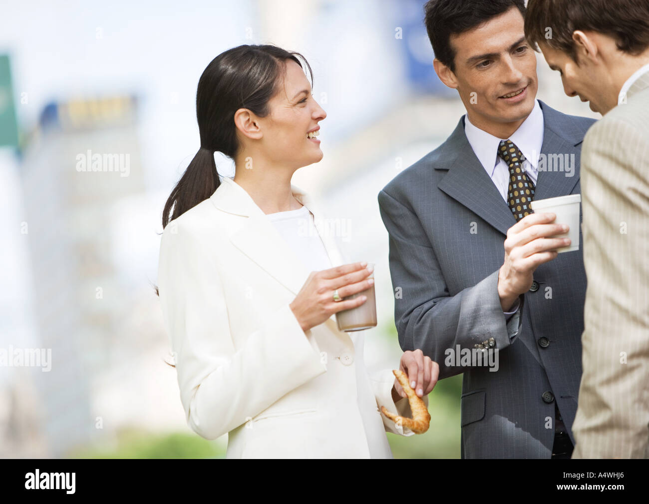 Business colleagues having coffee outdoors - Stock Image