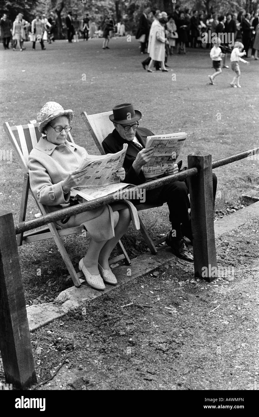 Older couple reading newspapers St James Park central London England 1971 HOMER SYKES - Stock Image