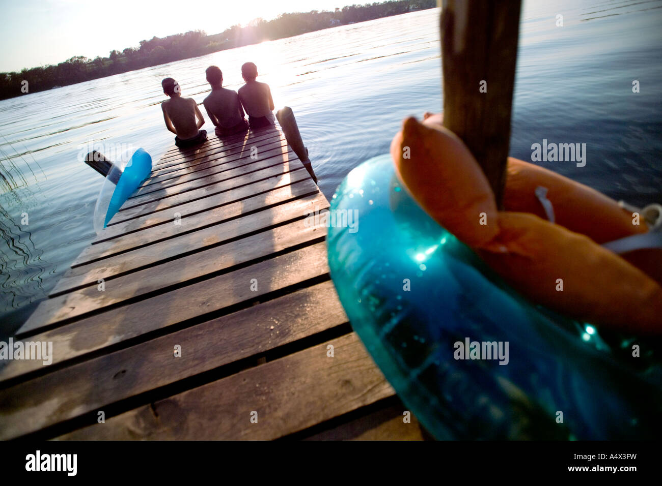 Kids sitting on a dock into a Lake Stock Photo