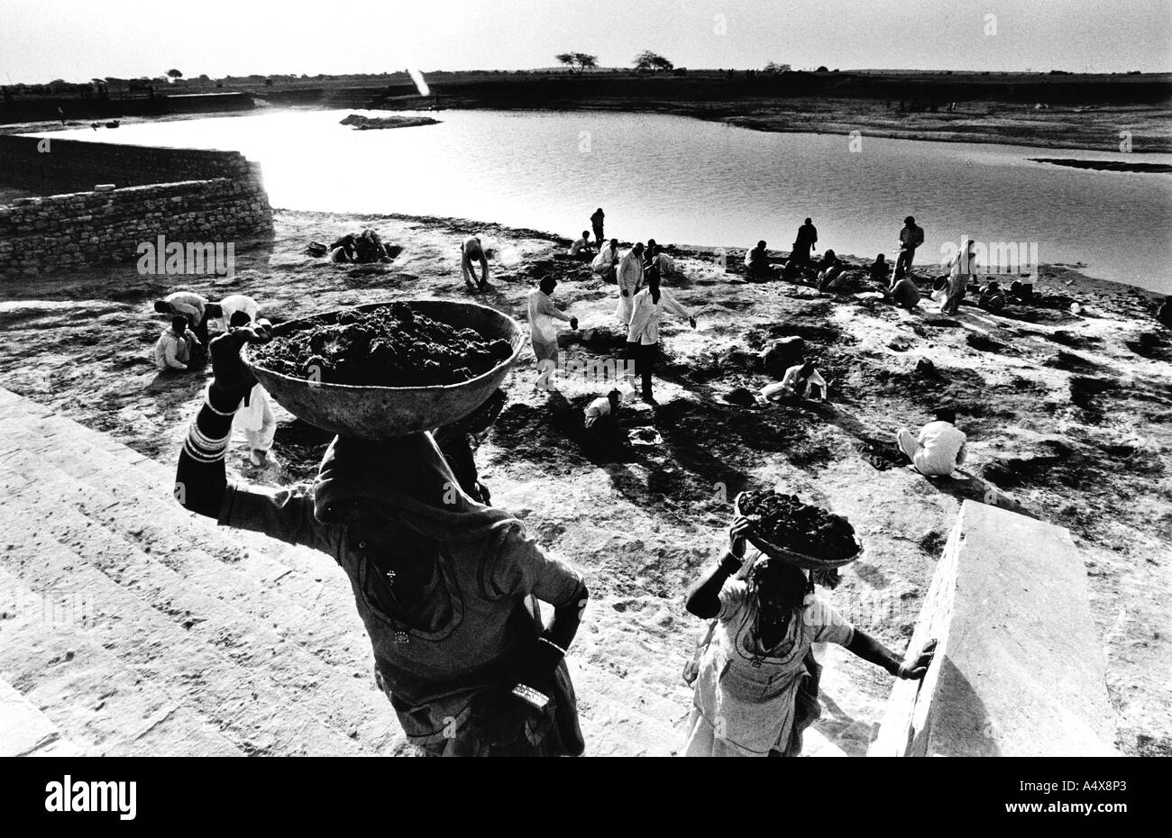 Construction workers digging near a pond in Rajasthan India - Stock Image