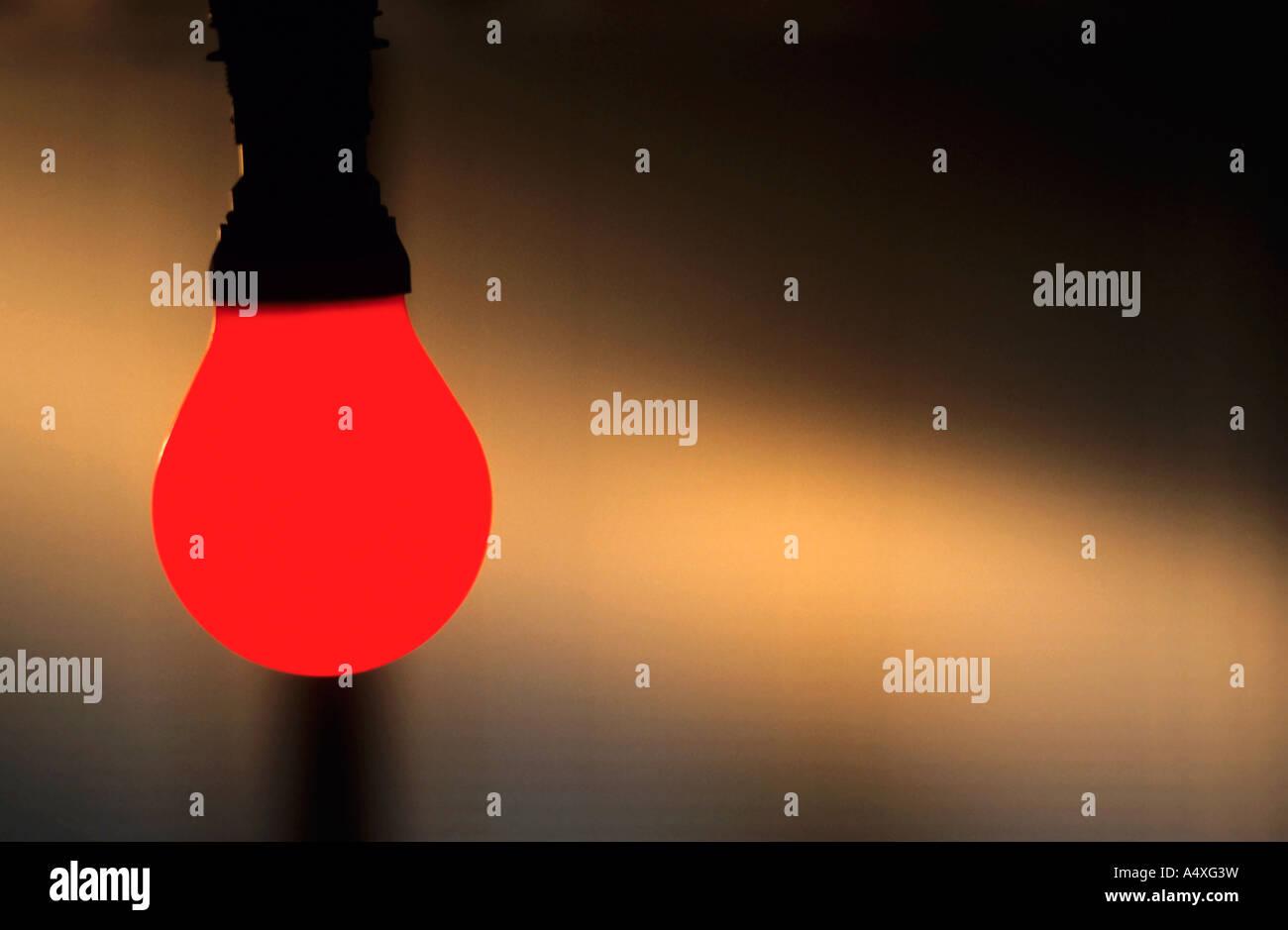 Illuminated red light bulb. - Stock Image