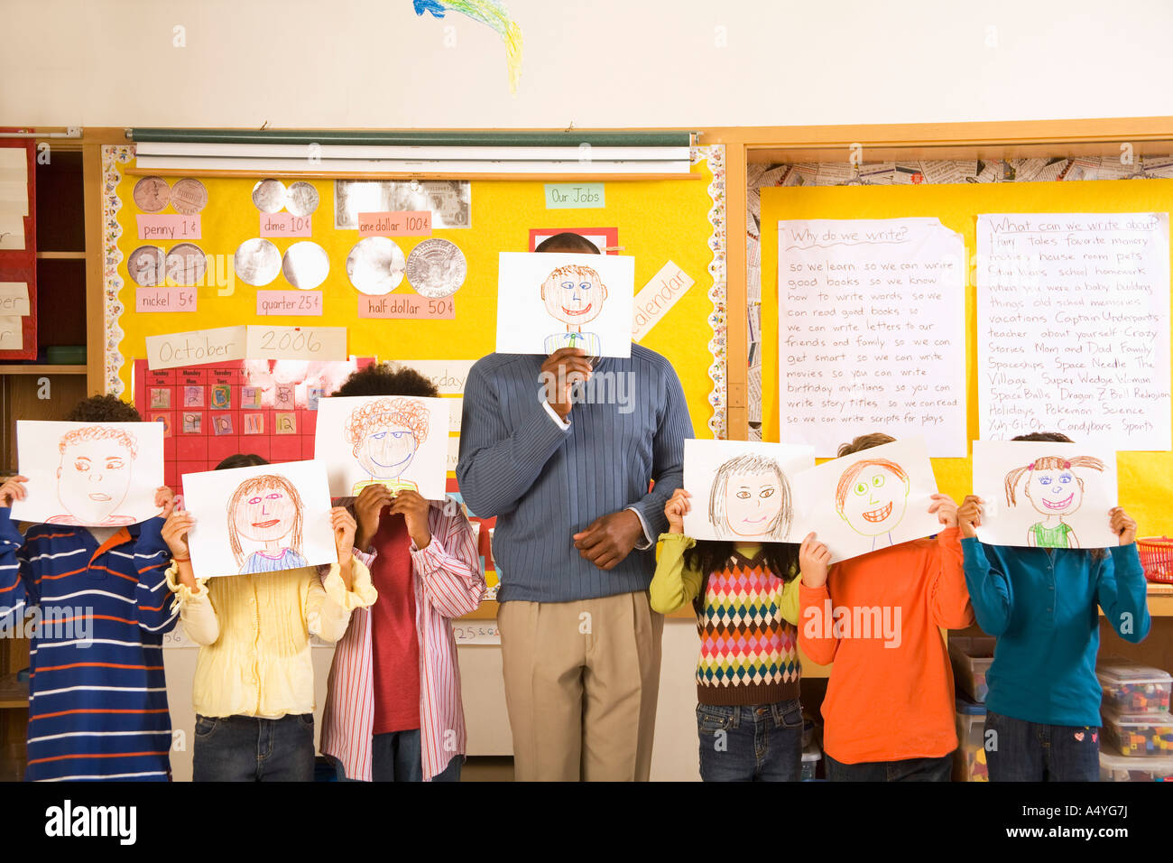 Male teacher and students holding drawings over faces - Stock Image