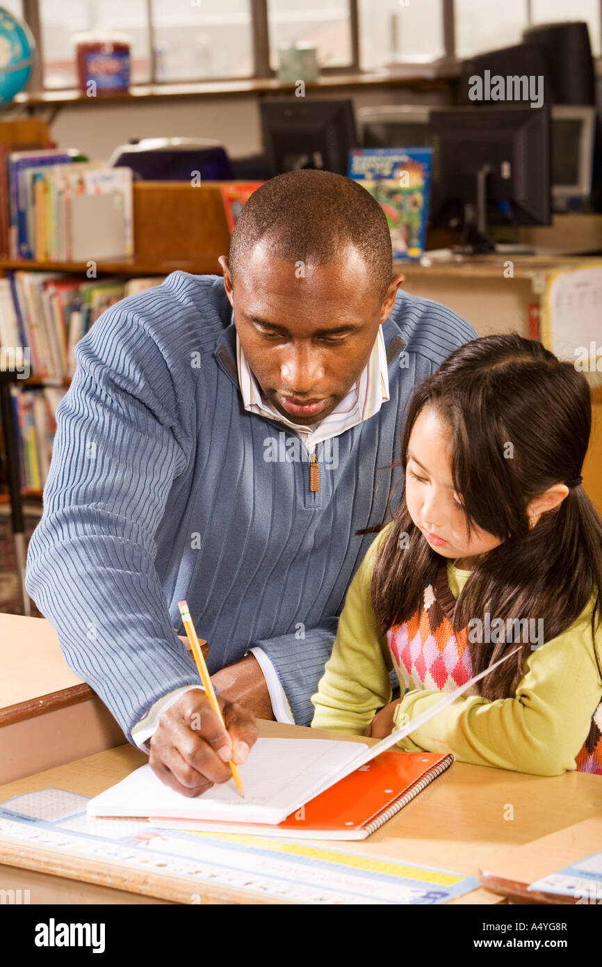Male teacher helping student - Stock Image