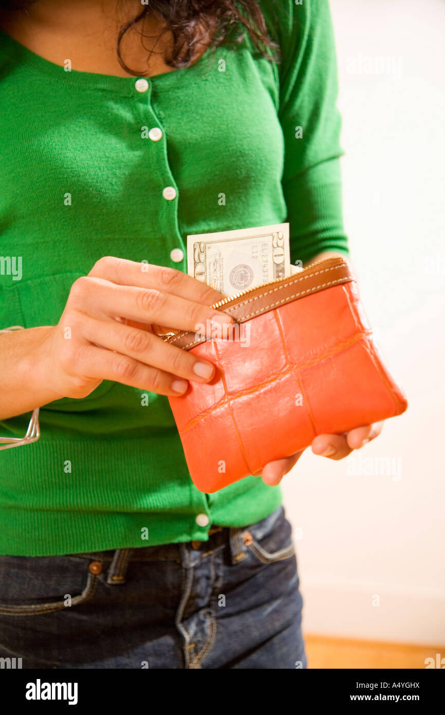 Woman taking money out of wallet - Stock Image