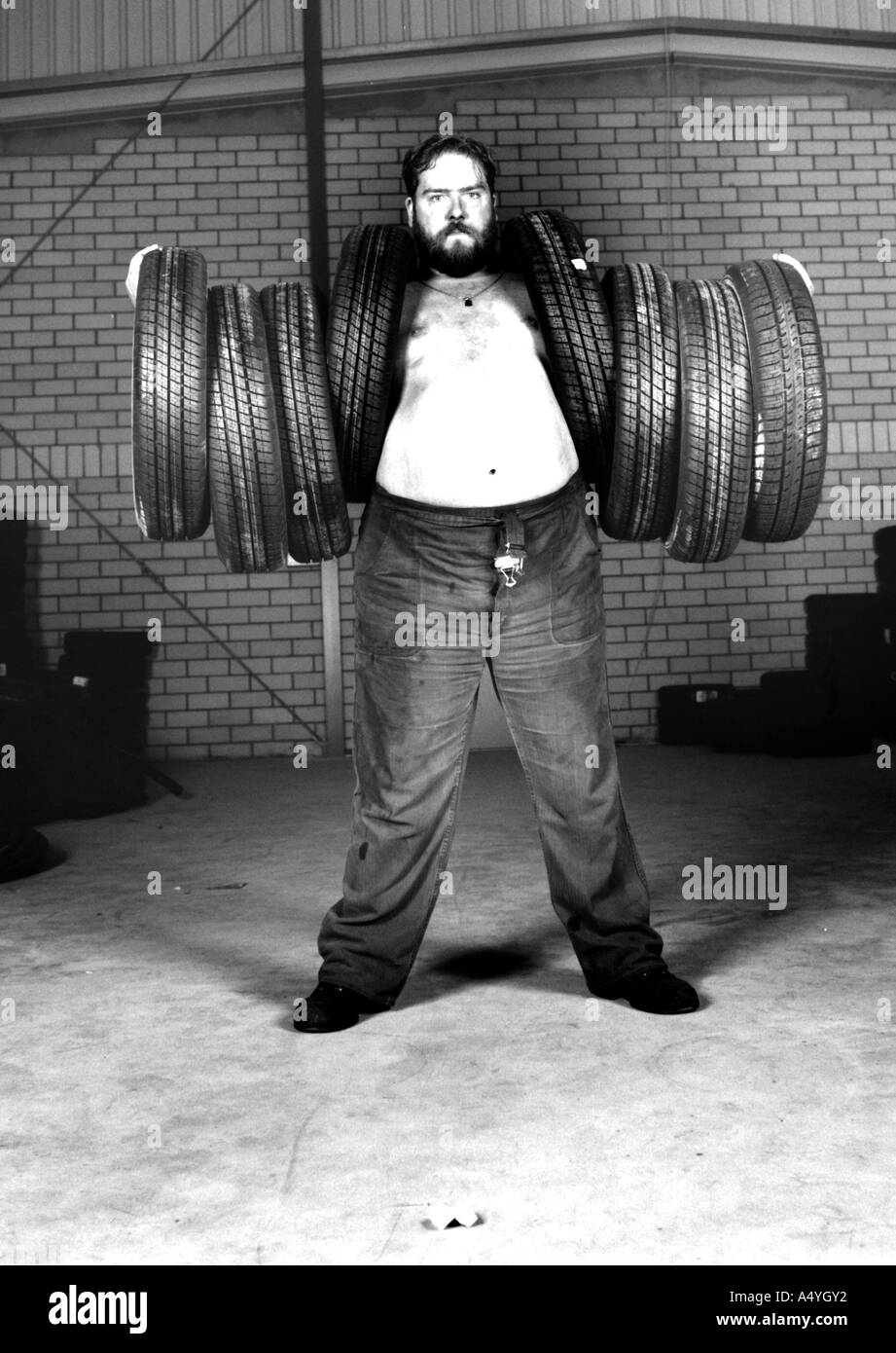 Man carrying 8 tyres - Stock Image