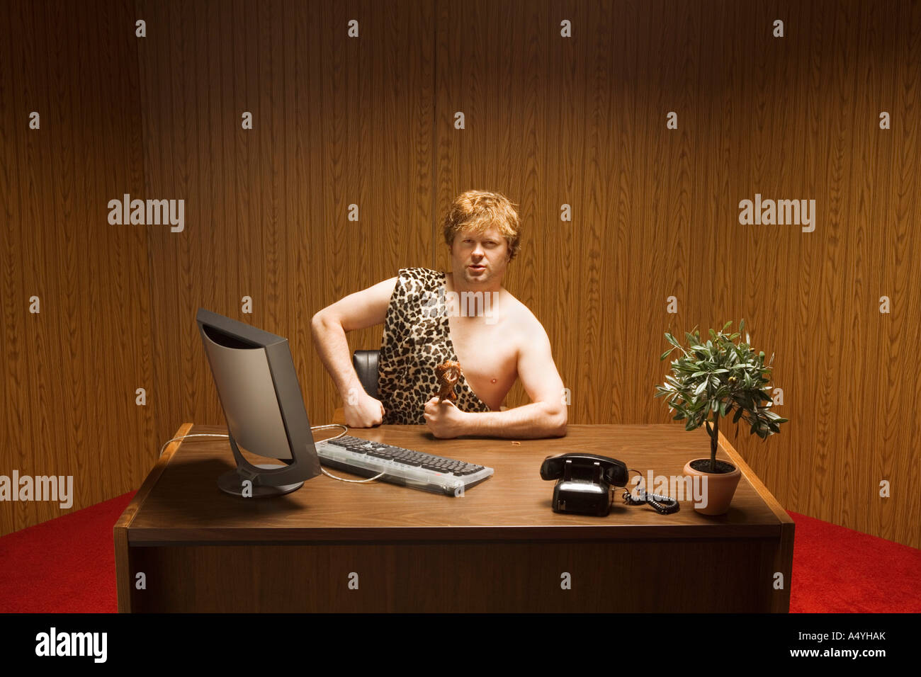 Businessman dressed as caveman at desk - Stock Image