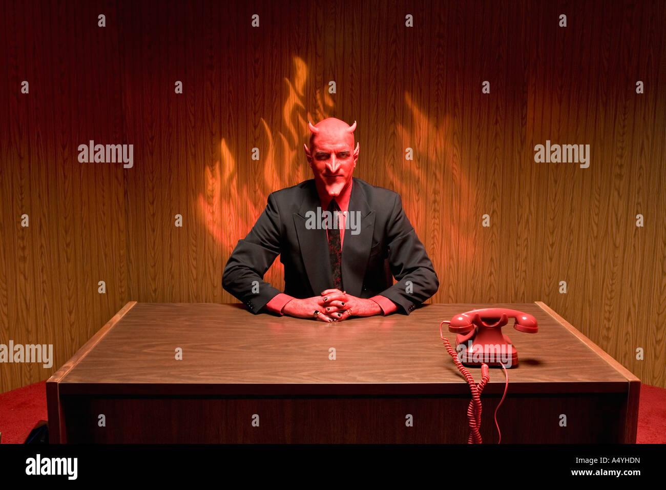 Businessman dressed as devil at desk - Stock Image