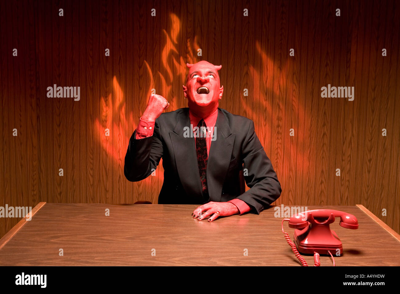 Businessman dressed as devil laughing - Stock Image