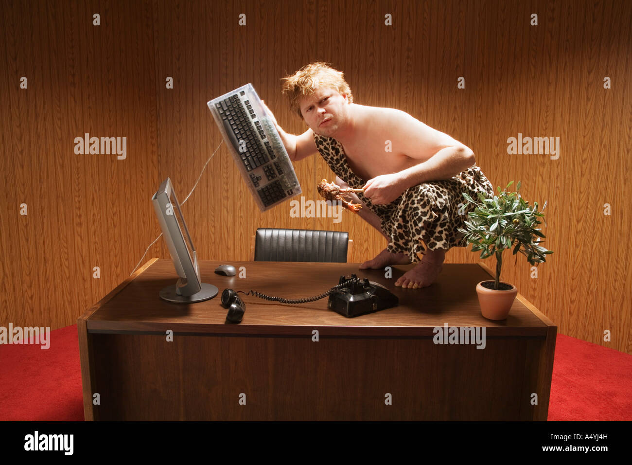 Businessman dressed as caveman crouching on desk - Stock Image