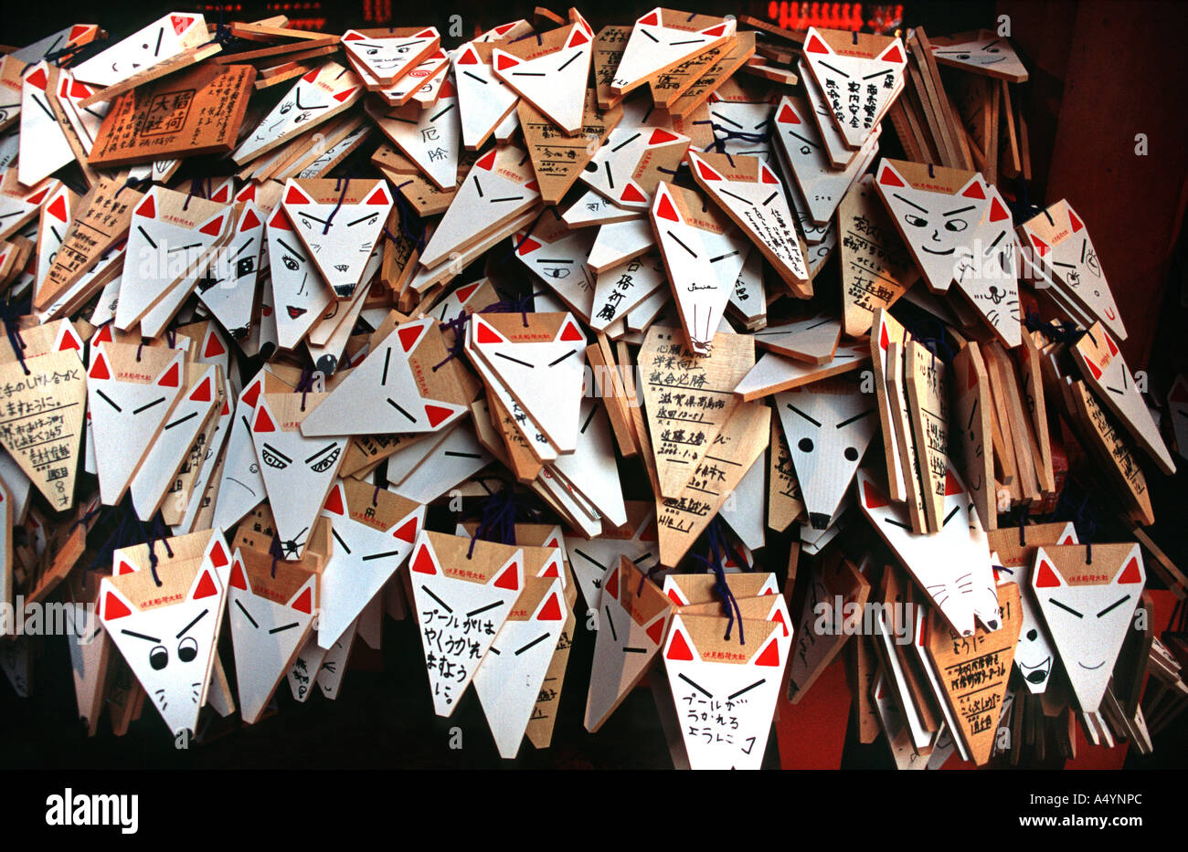 Wooden plaques in the shape of a fox heads with hand written wishes left at Fushimi Inari Taisha shrine in Kyoto JAPAN - Stock Image