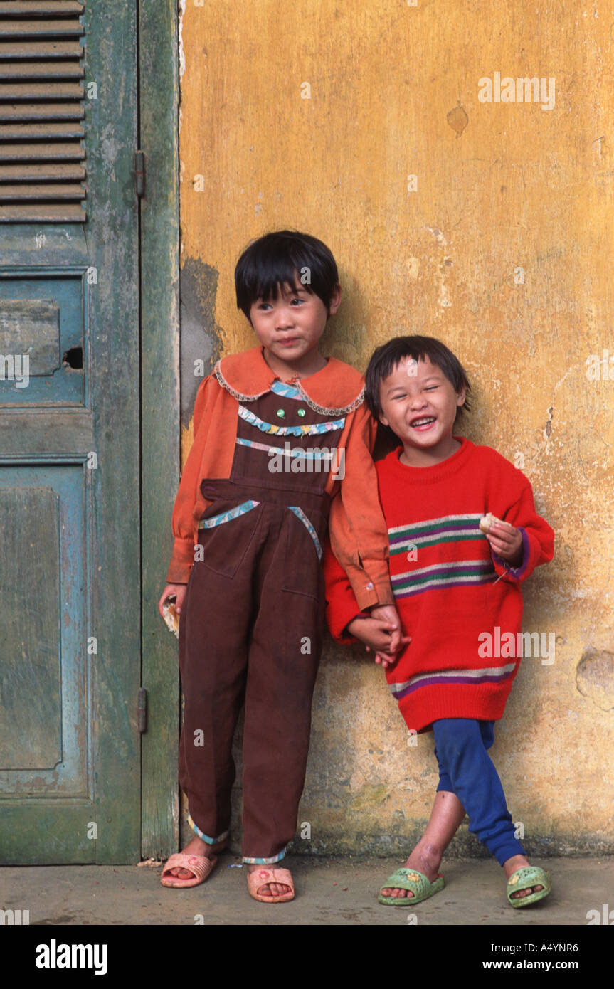 Vietnamese kids photographed against a yellow wall Sapa Vietnam - Stock Image