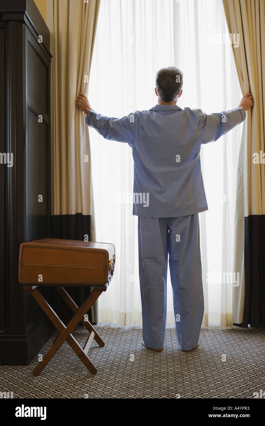 Man opening curtains - Stock Image