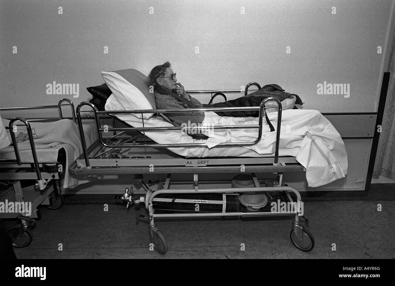 Elderly woman patient waiting on a bed in a corridor of the A&E department of Dudley Rd Hospital, Birmingham, - Stock Image