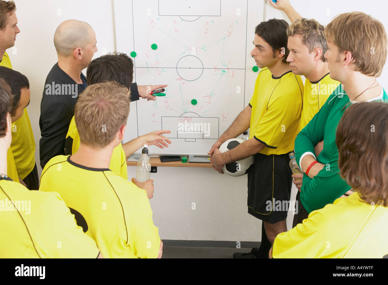 Coach discussing strategy with soccer team - Stock Image