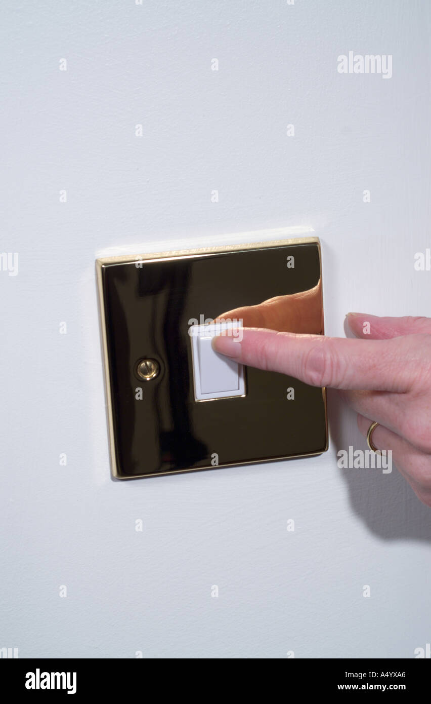 Operating a brass electric light switch - Stock Image