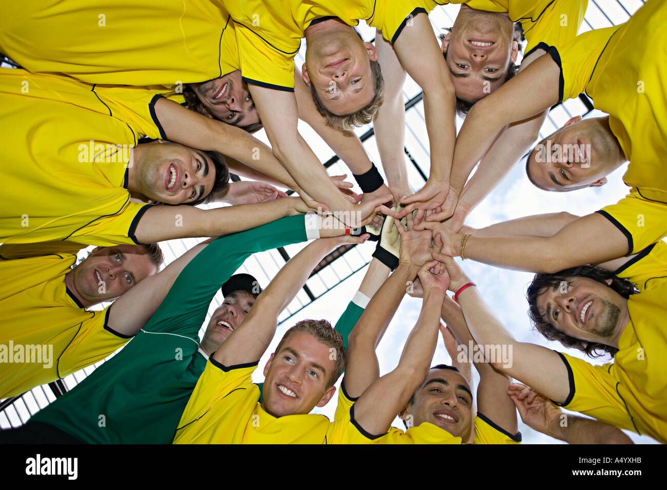 Football team putting hands together - Stock Image
