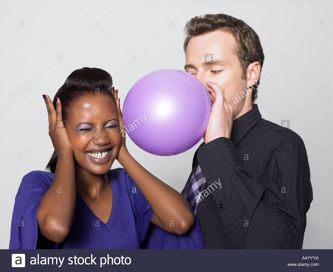 Woman scared of man blowing balloon - Stock Image