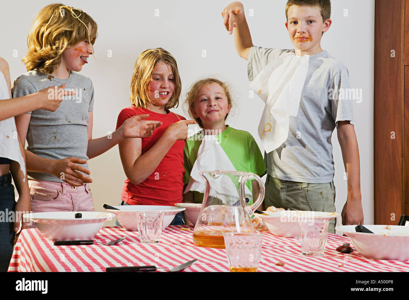 Messy children pointing at girl - Stock Image