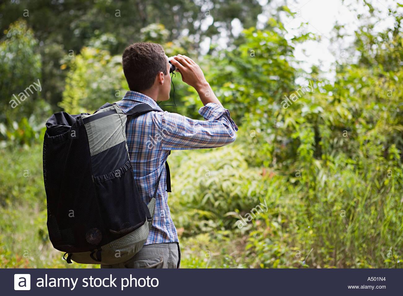 Young man looking through binoculars Stock Photo