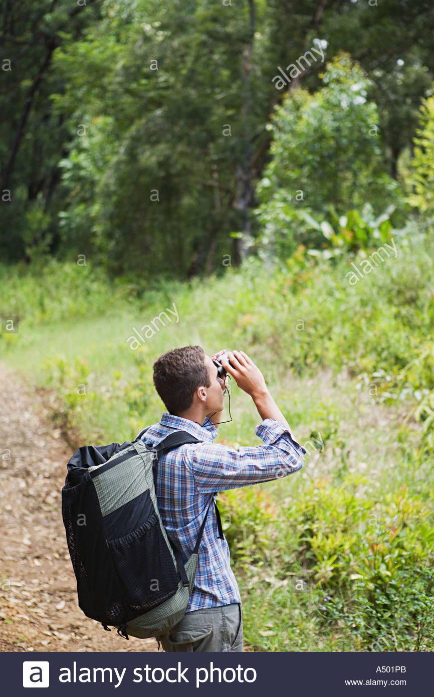 Young man looking through binoculars - Stock Image