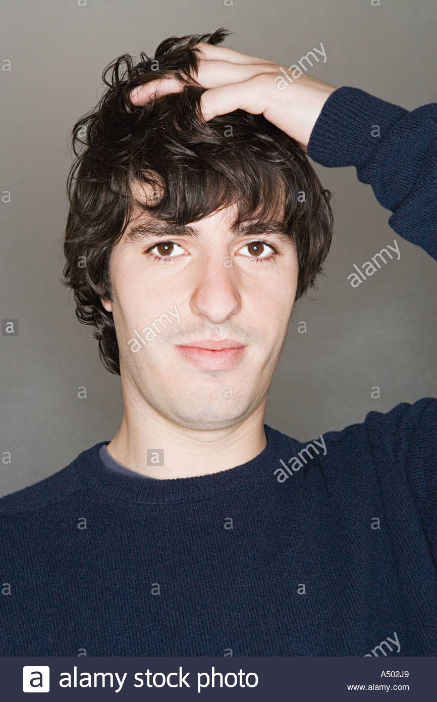 Young man with hand in hair - Stock Image