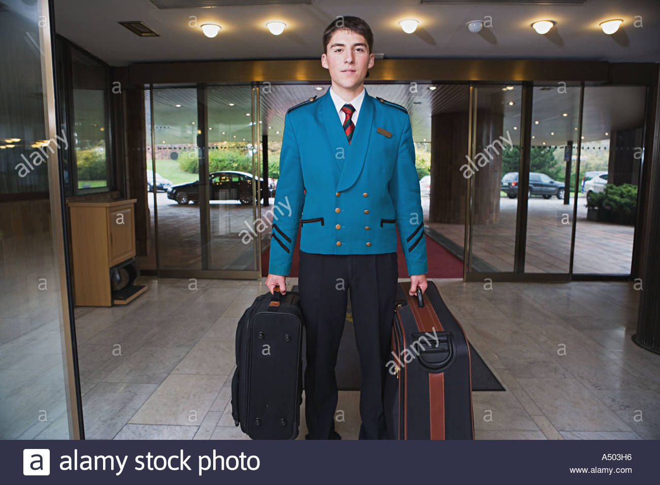 Bellboy carrying suitcases - Stock Image