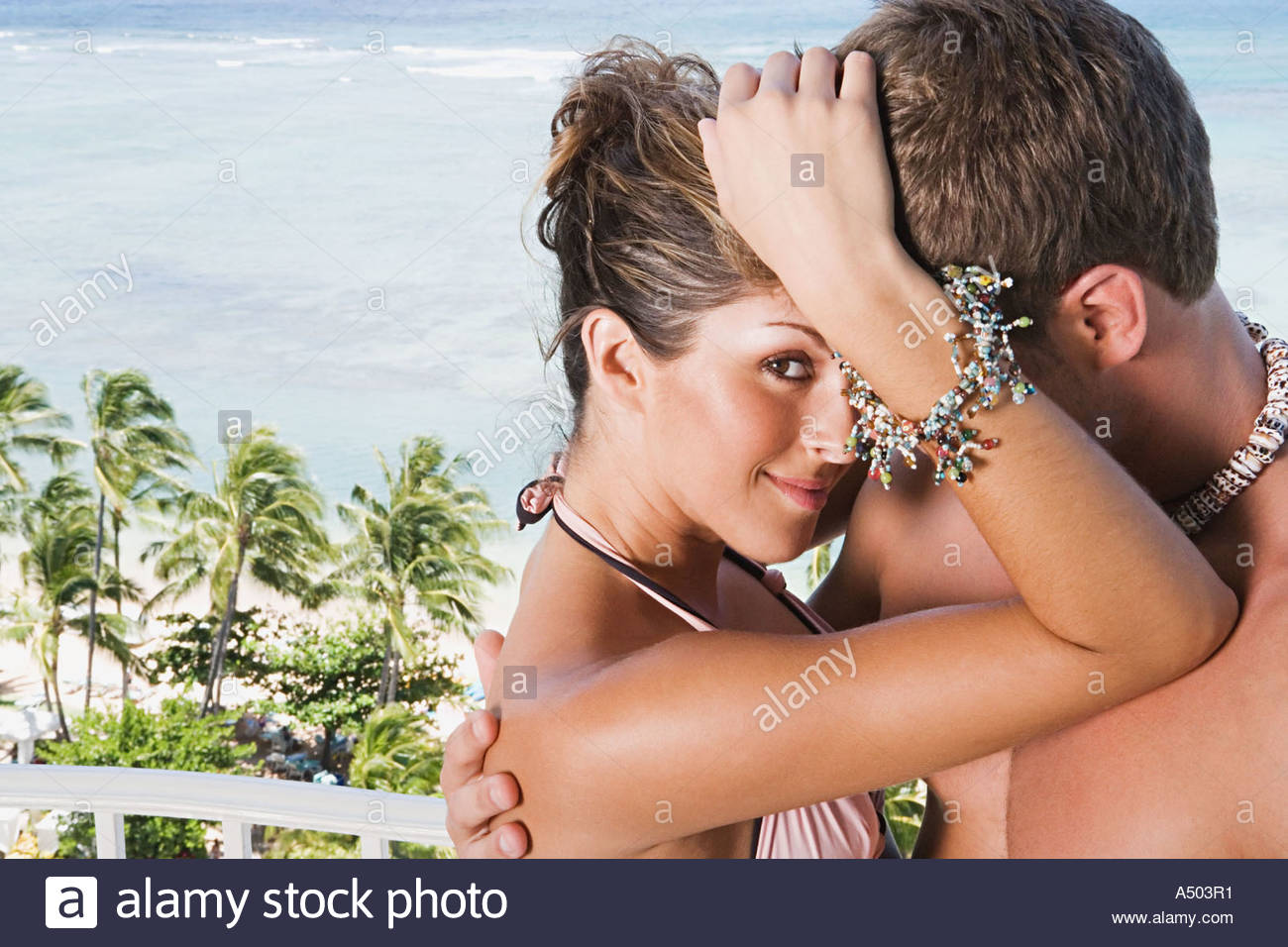 Couple embracing by ocean - Stock Image