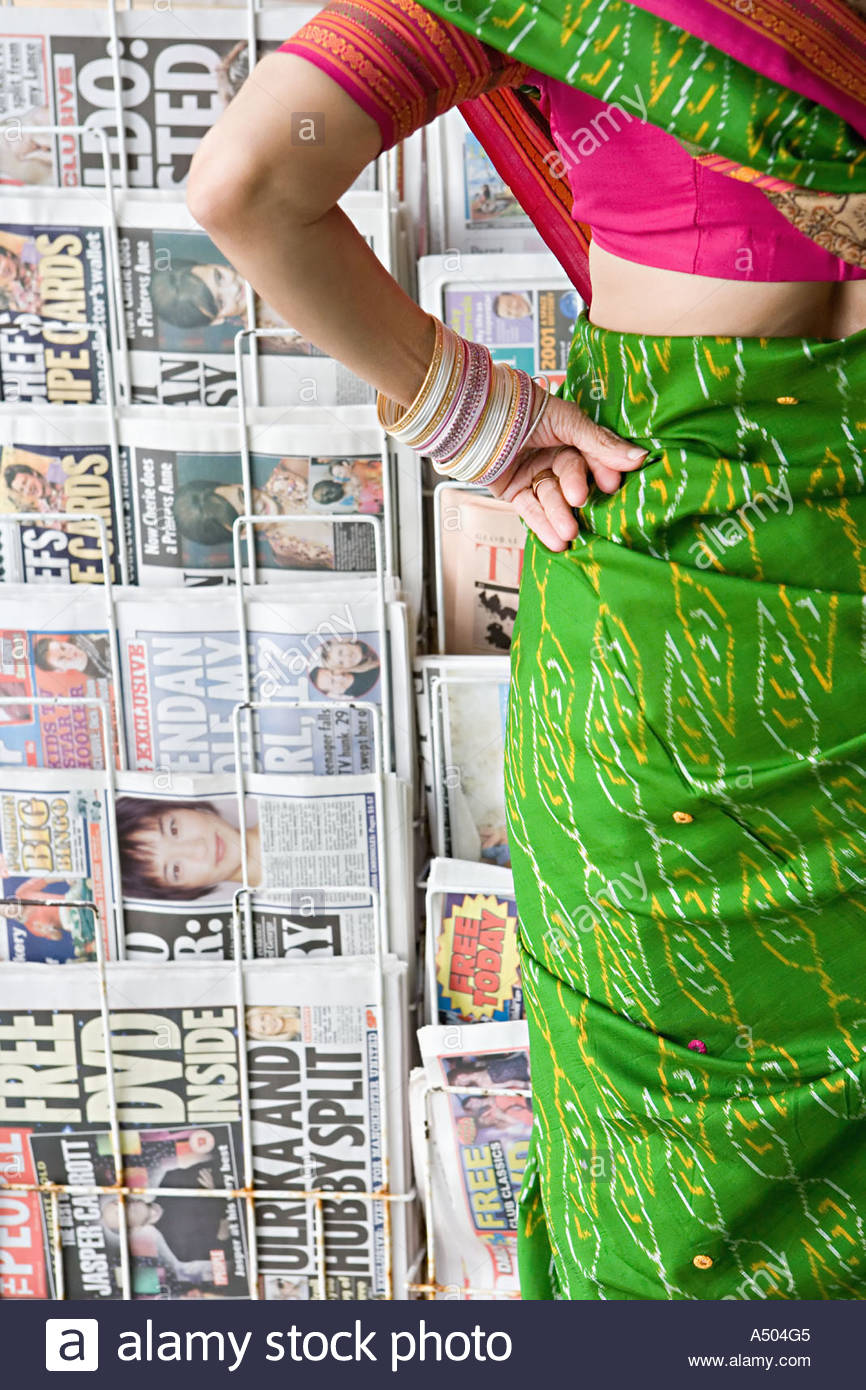 Woman in a sari by news stand - Stock Image