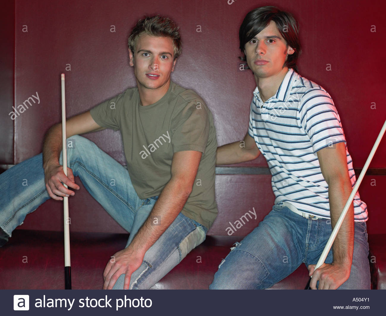 Two men sitting holding pool cues - Stock Image