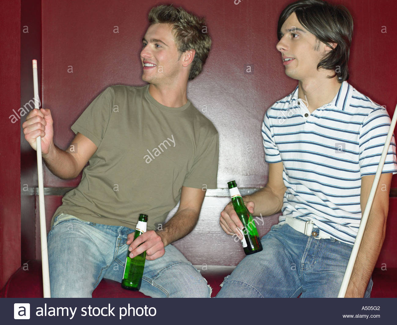 Two men sitting in a bar holding pool cues and drinks - Stock Image