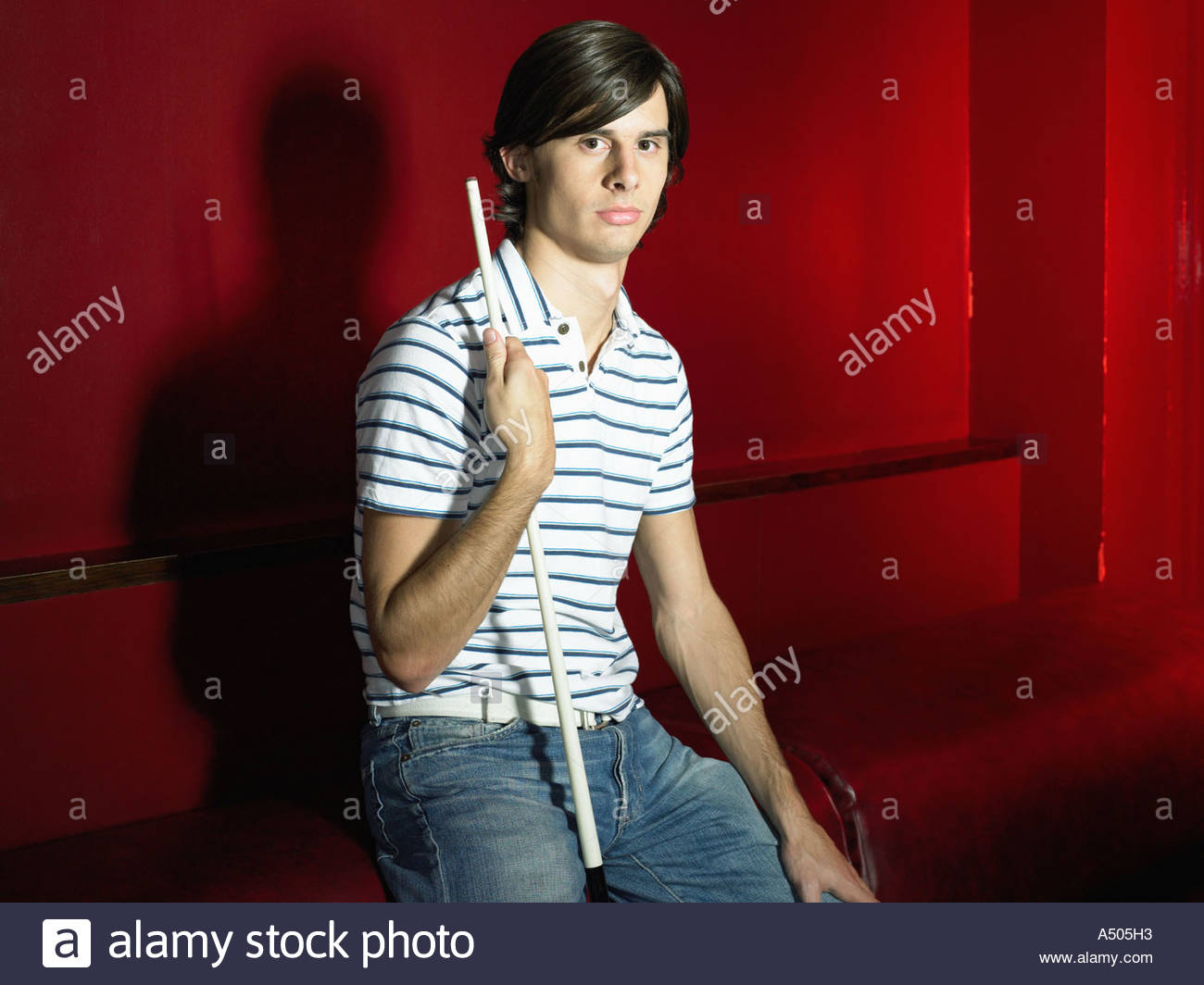 One man sitting in a bar holding pool cue - Stock Image