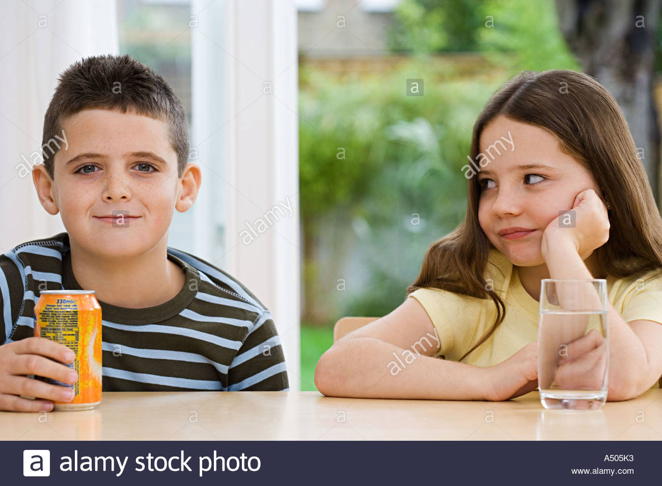 Boy with fizzy drink and girl with water - Stock Image