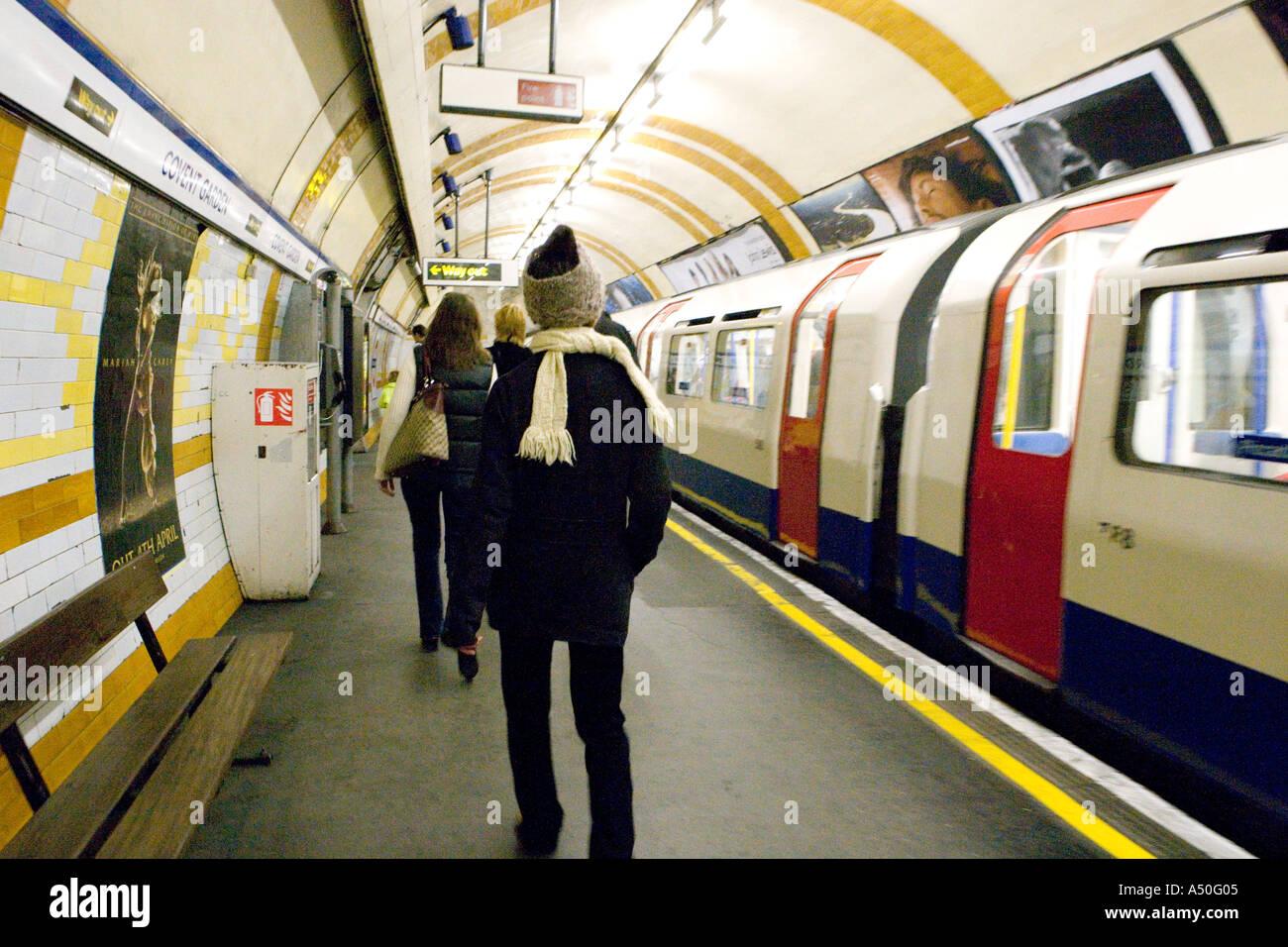 Tube train platform and commuters London England - Stock Image