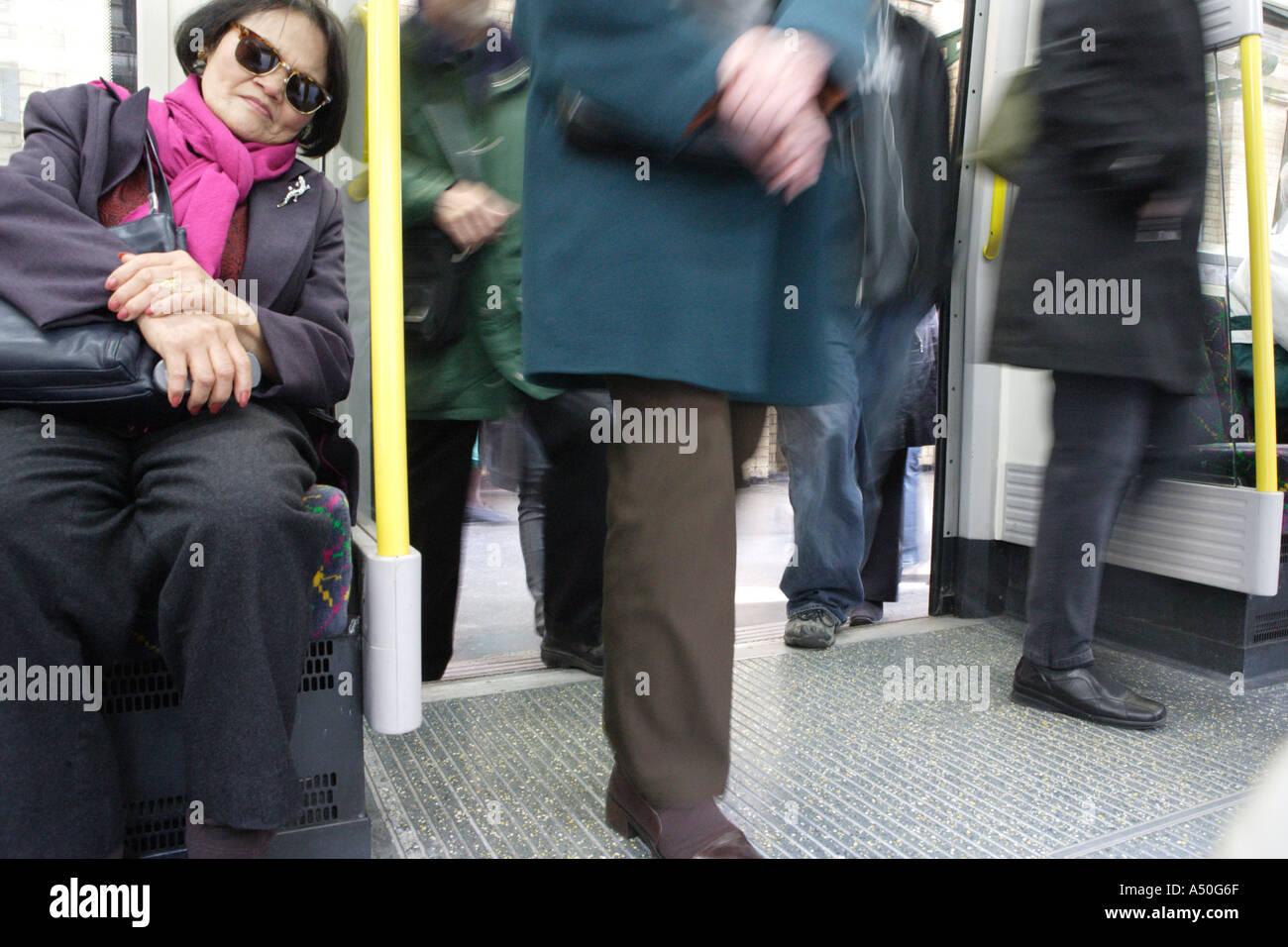 Commuters boarding a Tube train London England - Stock Image